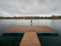 Man on stand up paddleboard. Athlete in wetsuit on paddleboard exploring the lake at cold weather against overcast sky royalty free stock photos