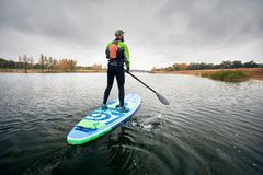 Man on stand up paddleboard. Athlete in wetsuit on paddleboard exploring the lake at cold weather against overcast sky stock image