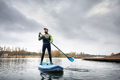 Man on stand up paddleboard. Athlete in wetsuit on paddleboard exploring the lake at cold weather against overcast sky royalty free stock photography