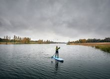 Man on stand up paddleboard. Man training on paddleboard in the lake against overcast sky stock image