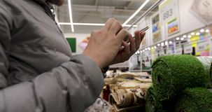 Man stand use phone hold ham in hardware store. Crop man in checks the goods in the application in the smartphone in the hardware store close up stock footage