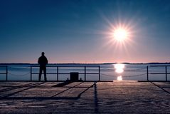 Man stand on wharf construction and looking at sea. Sunny clear blue sky, calm level Royalty Free Stock Photography