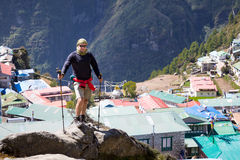 Man standing above mountain village. Stock Photos