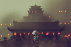 Man standing against ancient temple with red lights Royalty Free Stock Photography