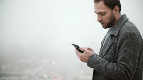 Man standing against the of Eiffel tower in Paris, France in foggy day. Handsome male using smartphone with touchscreen. Man standing against the background of stock video