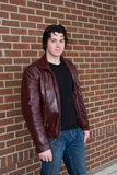 Man standing against a brick wall. Young man in a jacket standing against a brick wall royalty free stock photo