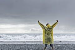 Man standing against the ocean. A man in a rain coat standing against the ocean stock photo