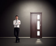Man standing against wall with door Stock Photography