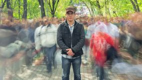 Man standing alone in blurred crowd, on background green trees. Time Lapse. The camera is approaching stock video footage