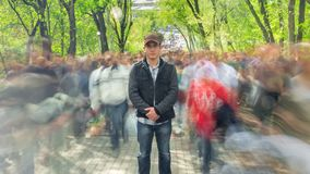 Man standing alone in blurred crowd, on background green trees. Time Lapse. The camera moves away. Full HD stock video footage