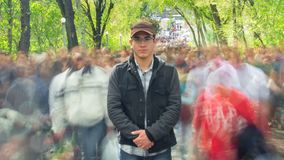Man standing alone in blurred crowd, on background green trees. Time Lapse. Full HD stock video