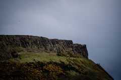 Man standing alone at Salisbury Crags in Edinburgh during a cloudy day, telephoto.  stock image