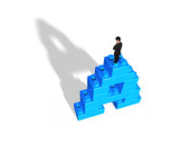 Man standing on alphabet letter A shape stack blocks Stock Image