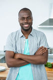 Man standing with arms crossed in kitchen Stock Photography