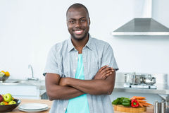 Man standing with arms crossed in kitchen Royalty Free Stock Image