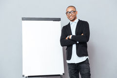 Man standing with arms crossed near flipchart. Smiling confident african man standing with arms crossed near flipchart Royalty Free Stock Photo