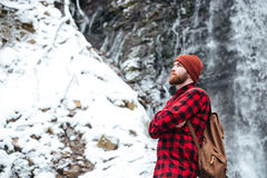 Man standing with arms crossed near mountain waterfall in winter Royalty Free Stock Image