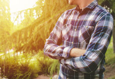Man standing with arms crossed in park. Man waiting in park. Stock Photo