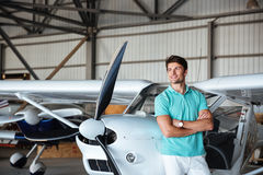 Man standing with arms crossed and smiling near small plane. Handsome young man standing with arms crossed and smiling near small plane stock photo