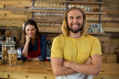 Man standing with arms crossed while waitress standing behind counter. In caf Royalty Free Stock Image