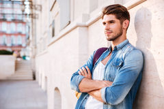 Man standing with arms folded and leaning on the wall Stock Image