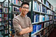 Man standing with arms folded in university library. Portrait of a smiling asian man standing with arms folded in university library and looking at camera stock images