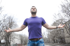 Man standing with arms raised outdoors. Concept about freedom, faith and celebration. Stock Image