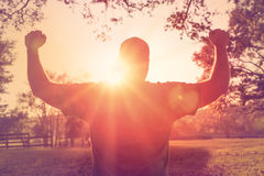 Man standing with arms raised in victory gesture. Successful happy accomplished man stands with raised arms facing the sun in victory gesture. White male athlete Royalty Free Stock Photo