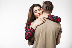 Man standing with back to camera, girlfriend hugging him romantically. royalty free stock photos