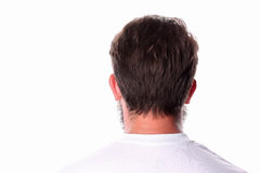 Man standing back in a white T-shirt. Close up. Man in a white T-shirt, portrait of a man, man's back isolated on white background, beard, white wall, unshaven royalty free stock images
