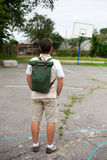 Man standing with backpack on his back at basketball court Royalty Free Stock Image