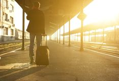 Man standing with bag and mobile phone at train station Royalty Free Stock Photos
