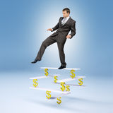 Man standing on balance with dollar sign Stock Photo