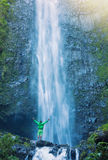 Man standing at base of massive waterfall Royalty Free Stock Photos
