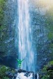 Man standing at base of massive waterfall royalty free stock photos