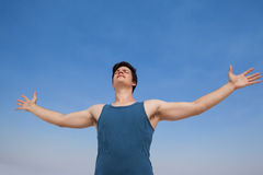 Man standing at beach with arms outstretched Stock Photography