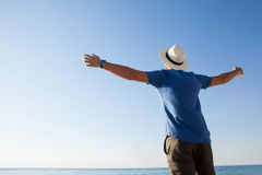 Man standing at beach with arms outstretched Royalty Free Stock Image