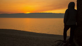 Man is standing on the beach and contemplates a beautiful sunset. Time lapse 4K stock video