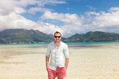 Man standing on the beach with hands in pockets Stock Photo