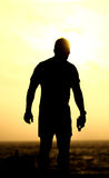 Man standing on the beach holding water bottle, silhouette view Stock Image