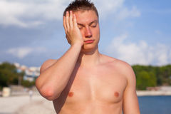Man standing on the beach and hurting because of headache. Royalty Free Stock Image