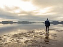 Man standing at the beach, reflections of the man in the water. Calm sea, mist and fog. Hamresanden, Kristiansand Royalty Free Stock Photography