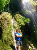 Man standing by beautiful waterfall in Romania. Male jungle hiker under water in deep forest Stock Images