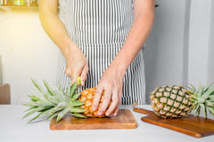 Man standing behind bar counter cutting a pineapple Royalty Free Stock Photos