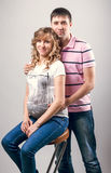 Man standing behind pregnant wife seated on chair Stock Photos
