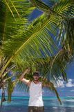 Man Standing Beneath Palm Tree on Tropical Beach. Young Man Holding on to Palm Fronds Beneath Palm Tree on Tropical Beach Royalty Free Stock Photo