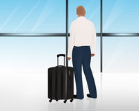 Man standing besides his luggage or suitcase at the airport window Stock Photos