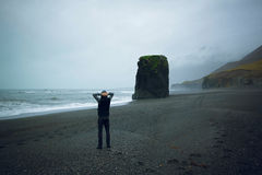 Man standing on black sand beach in Iceland. Man looking at ocean sea in a rainy day Stock Photos