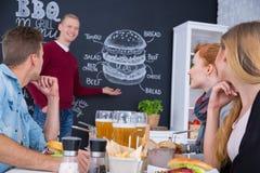 Man standing beside blackboard menu. Man standing beside blackboard burger menu, friends sitting at table Stock Image