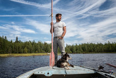 Man is standing on the boat with baddle in his hands and dog near of his legs Royalty Free Stock Photos